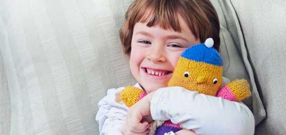 Child hugging toy banner image
